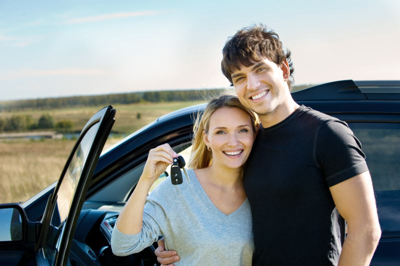 portrait of happy beautiful couple showing the keys standing near the car